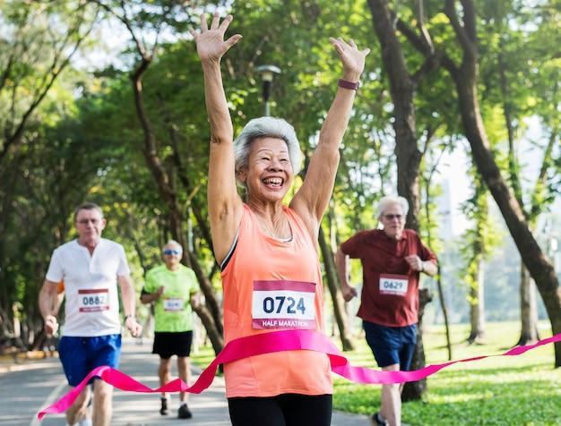 Happy senior running through the finish line Premium Photo