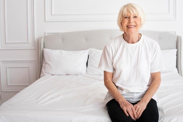Happy senior sitting on bed Free Photo