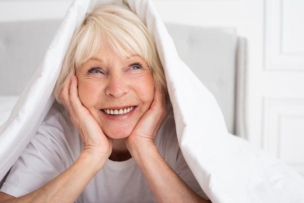 Happy senior sitting under blanket Free Photo