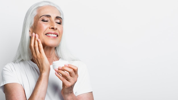 Happy senior woman applying cream Free Photo