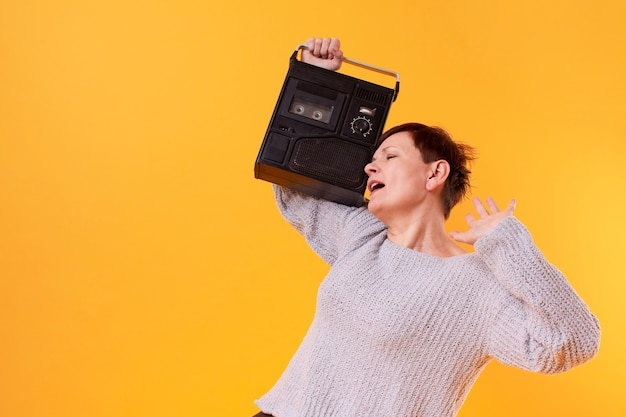Happy senior woman listening music from a cassette player Free Photo