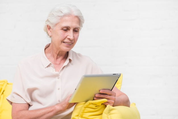 Happy senior woman looking at digital tablet against white wall Free Photo