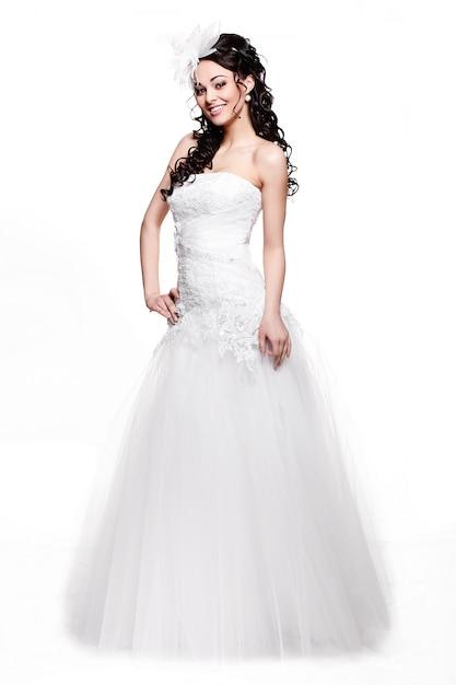 Счастливая сексуальная красивая невеста брюнетка женщина в белом свадебном платье с прической и ярким макияжем во всю длину в стиле ретро Бесплатные Фотографии