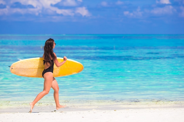 Happy shapely surf woman at white beach with yellow surfboard Premium Photo
