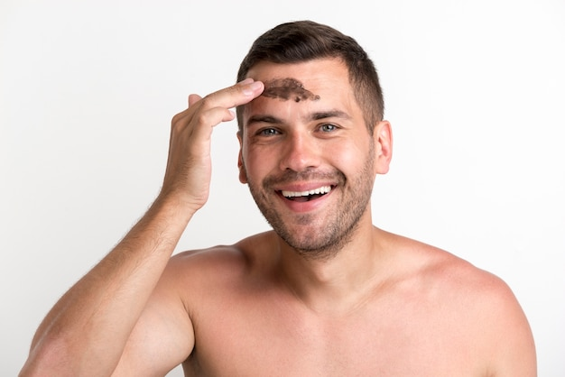 Happy shirtless young man applying black mask on face against white background Free Photo
