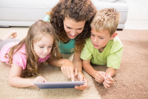 Happy siblings lying on the rug using tablet with their mother Premium Photo