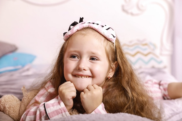 Happy smiles redhead girl child is lying on the bed sheets on the huge bed dressed in pink pajamas Free Photo