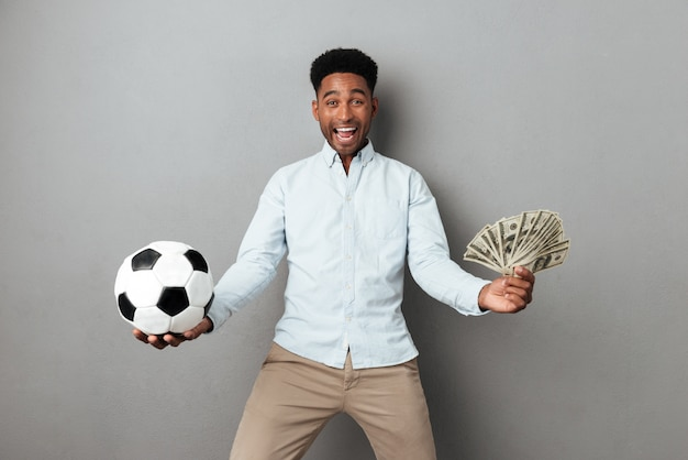 Happy smiling african man holding football and money banknotes Free Photo