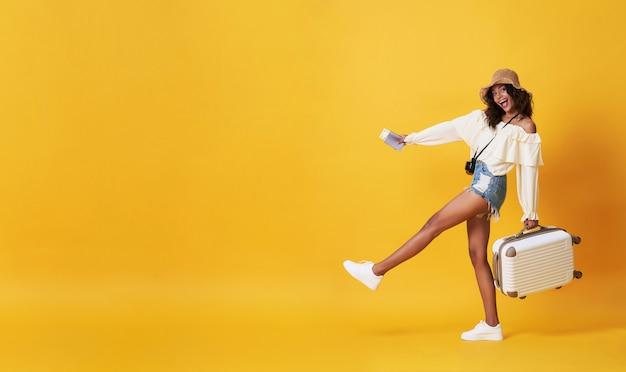 コピースペースと黄色で彼らの夏休みの休暇を楽しんで荷物で夏服に身を包んだ幸せな笑顔のアフリカの女性。 Premium写真