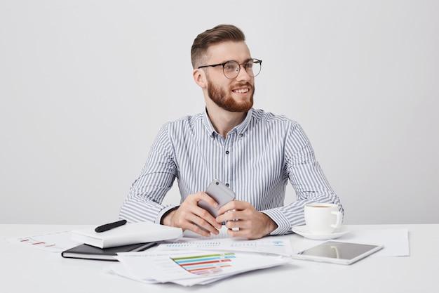 幸せな笑みを浮かべてひげを生やした青年実業家が同僚に気づかれないように見える、現代のスマートフォンで職場に座っています。 無料写真