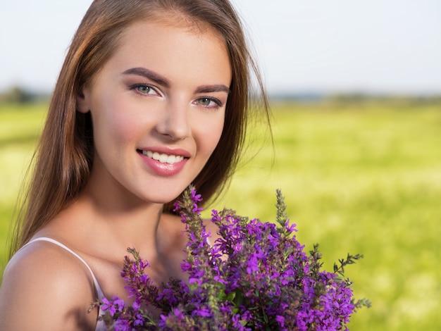 Bella donna felice e sorridente all'aperto con fiori viola nelle mani. la giovane ragazza allegra è sulla natura sopra il campo di primavera. concetto di libertà. ritratto di un modello carino e sexy sul prato Foto Gratuite