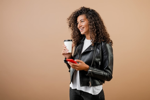 Happy smiling black girl with phone and coffee to go cup isolated over brown Premium Photo