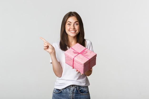 생일 선물을 들고 로고에서 왼쪽 손가락을 가리키는 행복 웃는 갈색 머리 소녀. 프리미엄 사진