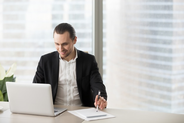 Happy smiling businessman in office looking at laptop sreen. Free Photo