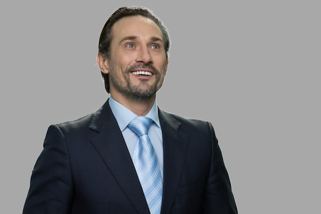 思いやりのある表情で幸せな笑顔のビジネスマン。灰色の背景に魅力的な空想のビジネスパーソン。将来の成功を夢見ています。 Premium写真
