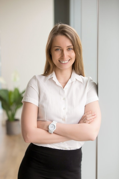 Happy smiling businesswoman looking at camera with arms crossed, portrait Free Photo