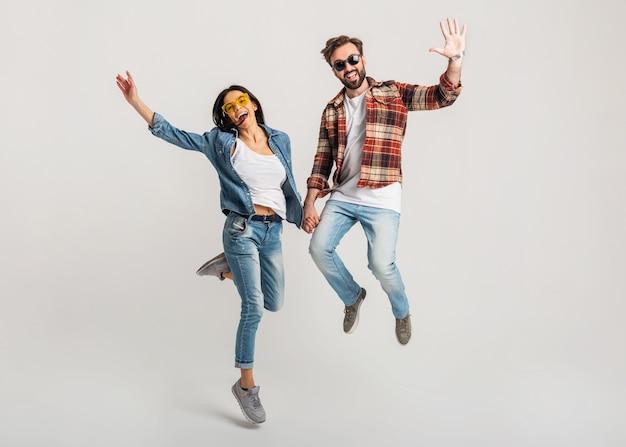 Счастливая улыбающаяся пара изолировала активные прыжки на белой студии Бесплатные Фотографии