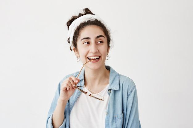Счастливая улыбающаяся темноволосая женщина в до-тряпке в джинсовой рубашке, с очками, имеет хорошее настроение после получения хороших новостей, рада встрече с друзьями и родственниками. люди, счастье, концепция выражения лица Бесплатные Фотографии