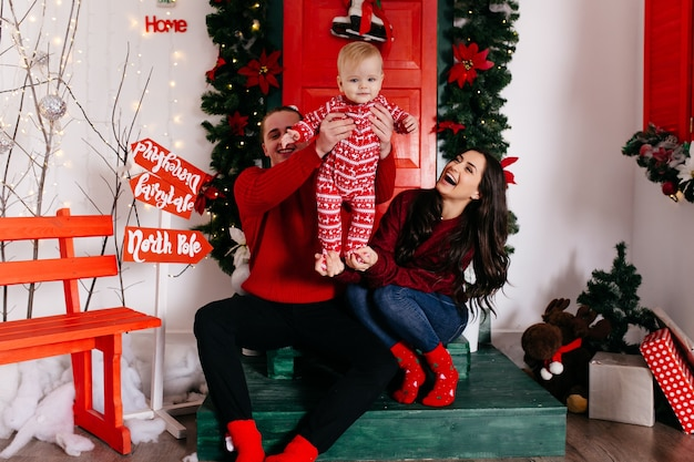 Happy smiling family at studio on background of the christmas tree with gift Free Photo