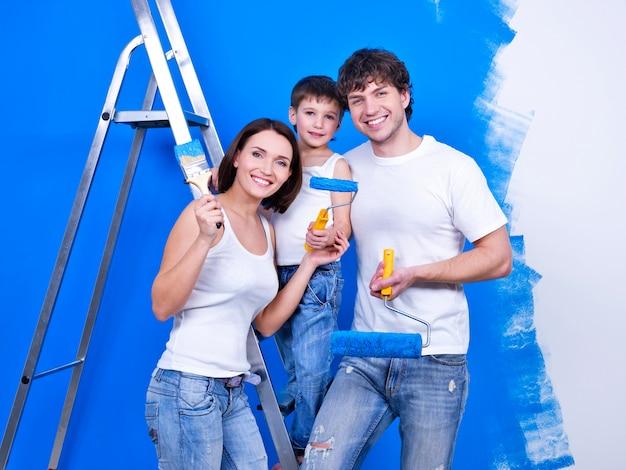 Famiglia sorridente felice con i pennelli facendo lavori di ristrutturazione - al chiuso Foto Gratuite