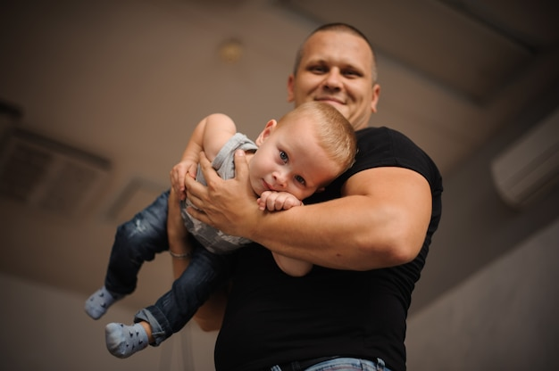 Happy smiling father holding a son in his hands Premium Photo