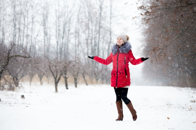 Happy smiling female in red winter jacket enjoys the snow, outdoors, in park Free Photo