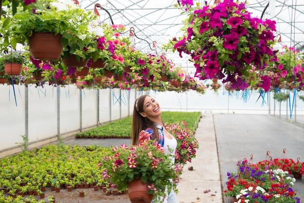 행복 미소 플로리스트 꽃을 배열하고 온실 정원에서 일을 즐기는 무료 사진