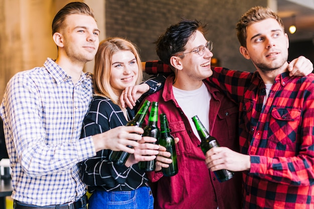 Happy smiling friends holding the green beer bottles in hand Free Photo