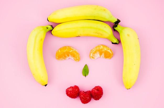 Happy smiling fruit face on light surface Free Photo