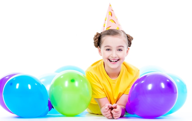 Happy smiling girl in yellow t-shirt  lying on the floor with colorful balloons - isolated on a white. Free Photo