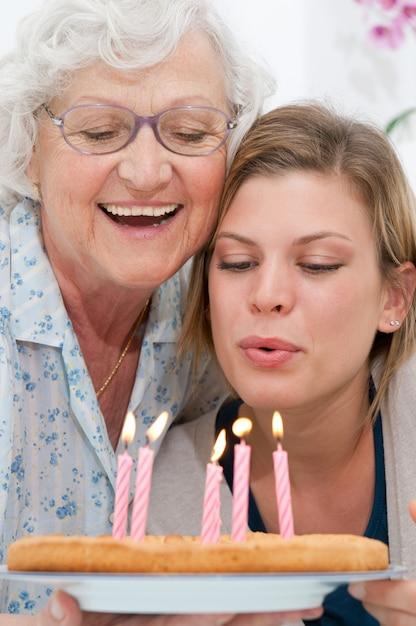 Счастливая улыбающаяся бабушка празднует и дарит внуку праздничный торт дома Premium Фотографии
