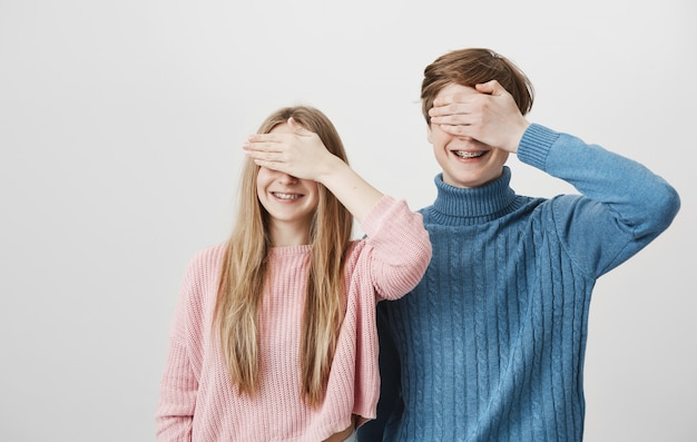 Happy smiling guy and girl with braces close eyes with palms Free Photo