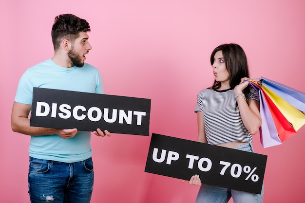 Happy smiling handsome couple man and woman with discount up to 70% sign and colorful shopping bags Premium Photo