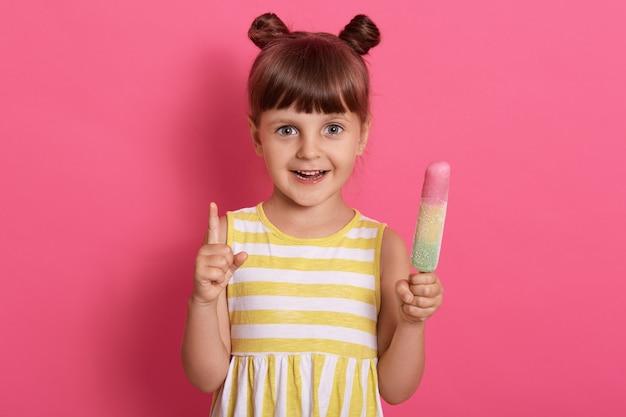 Счастливая усмехаясь девушка ребенк держа мороженое и указывая вверх с ее указательным пальцем, нося платье лета с белыми и желтыми нашивками. Бесплатные Фотографии