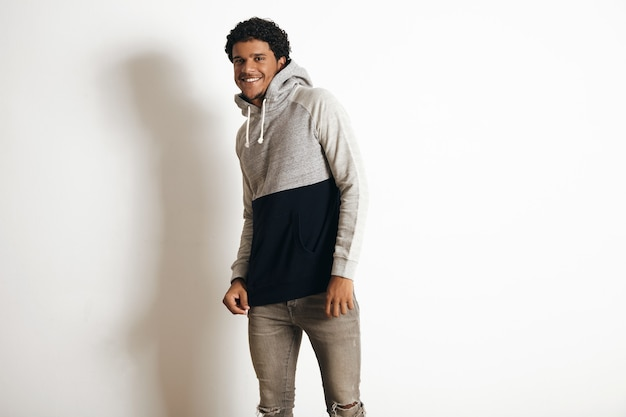 Happy smiling latino guy wears blank grey black sweater with hood and distressed jeans, isolated on white Free Photo