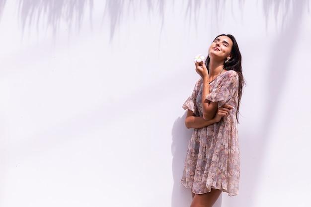 La donna dai capelli lunghi sorridente felice in vestito si leva in piedi sul muro bianco Foto Gratuite