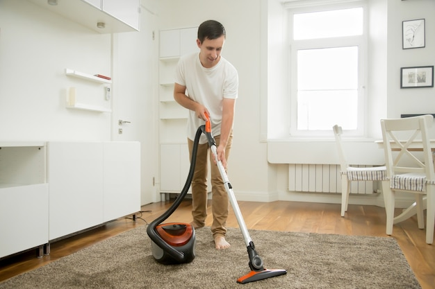 Happy smiling man cleaning the carpet Free Photo