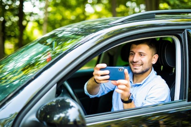 スマートフォンで車を運転して屋外の状況の写真を撮ると幸せな笑みを浮かべて男 Premium写真