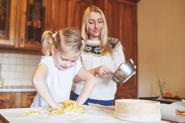 台所で幸せな笑顔のお母さんは彼女の娘と一緒にクッキーを焼きます。 無料写真