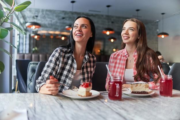 Счастливая улыбающаяся мать и радостная дочь-подросток едят пирожные и хорошо проводят время вместе в кафе Premium Фотографии
