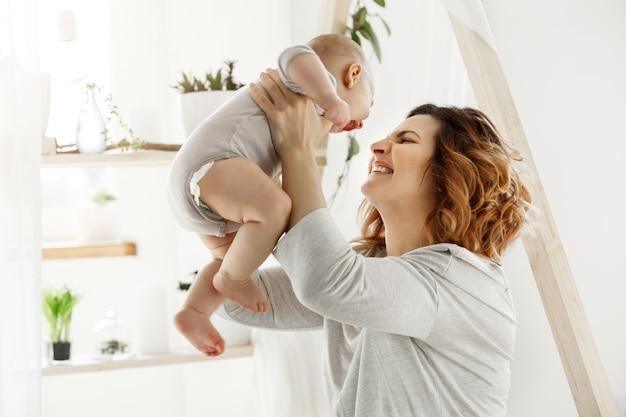 Madre sorridente felice che gioca con il bambino neonato in camera da letto leggera comoda davanti alla finestra. momenti di felicità maternità con i bambini. concetto di famiglia. Foto Gratuite