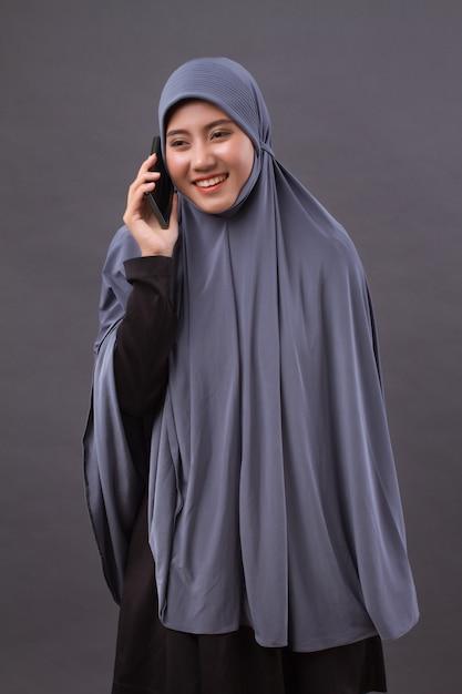 Happy smiling muslim woman using smartphone call, wireless internet device Premium Photo