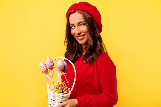 孤立した黄色の壁の上にイースターバスケットでポーズをとって赤いプルオーバーと赤いベレー帽を身に着けている巻き毛の幸せな笑顔のきれいな女性 無料写真