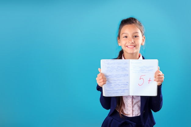 Happy smiling schoolgirl in uniform holding and showing notebook with excellent results of test or exam Premium Photo