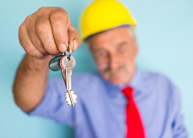 Happy smiling senior architect holding keys for ready  new house Premium Photo