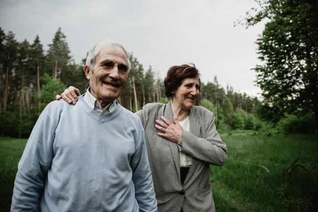 自然を愛し、楽しんで、幸せな笑顔のシニアカップル。緑の野原にいる老夫婦。春の森を歩いて抱き締めるかわいい年配のカップル Premium写真