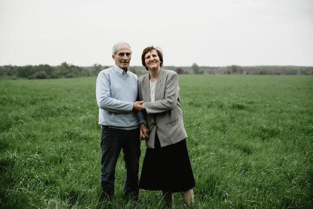 Счастливый улыбающийся старший пара в любви на природе, весело. пожилая пара на зеленом поле. милая пара старших гулять и обниматься в весеннем лесу Premium Фотографии