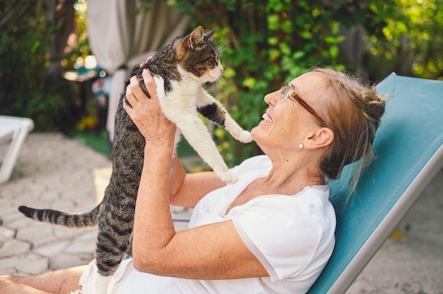 国内のぶち猫を抱いて屋外の夏の庭でリラックスしたメガネで幸せな笑顔の年配の女性。引退した老人と動物のペットの概念 Premium写真