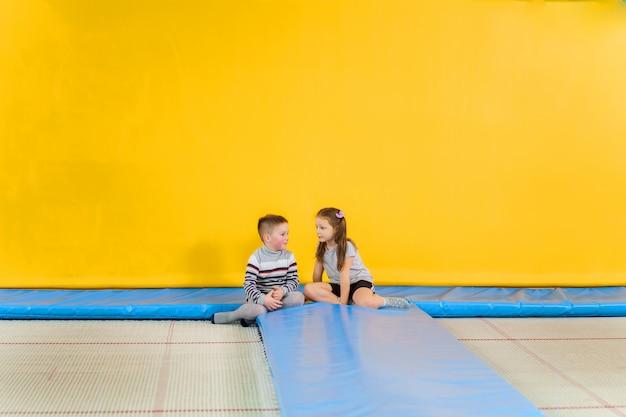Счастливые улыбающиеся маленькие дети прыгают на батуте в помещении в развлекательном центре Premium Фотографии