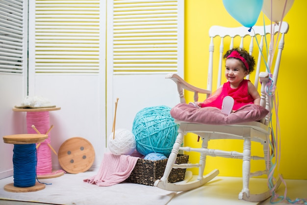 Happy smiling sweet baby girl sitting on armchair with birthday balloons Premium Photo